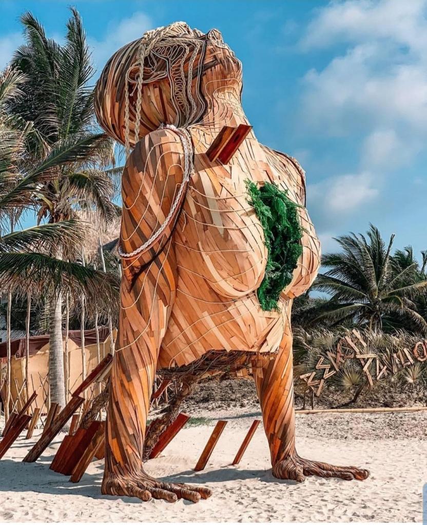 giant wooden sculpture of an upper body doing yoga