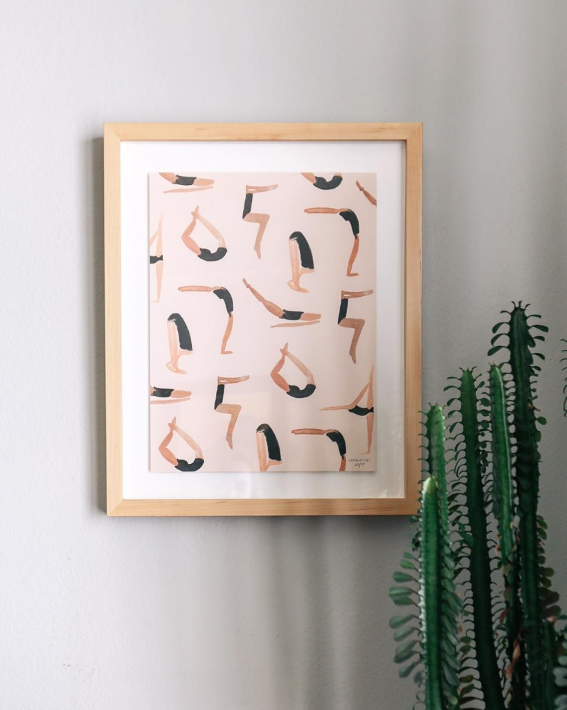 abstract yoga art painting of people doing yoga with beige frame and hanging beside a tall cactus