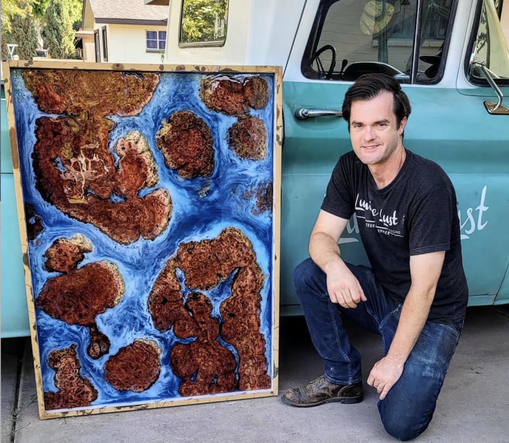 Ryan, the owner of Lumberlust Designs, sits beside an oceanic resin tabletop.