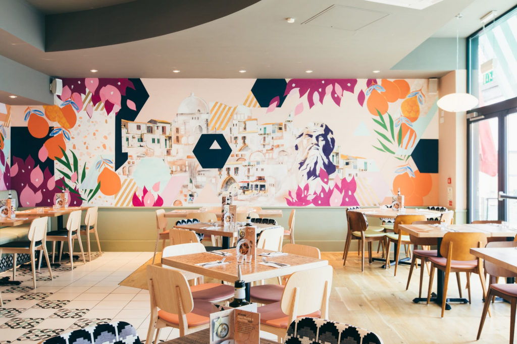 A large vibrant mural depicting a city and geometric shapes created by Hannah Adamaszek for ASK Italian.
