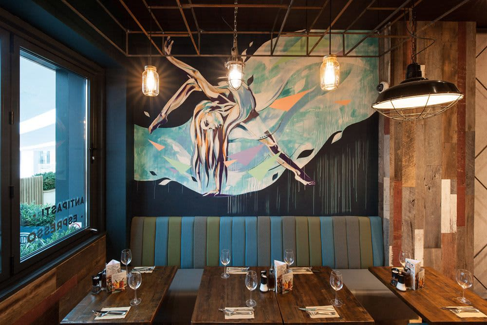A mural painted by Hannah Adamaszek in the Zizzi Hull restaurant depicting a dancer engulfed by a moving sea.