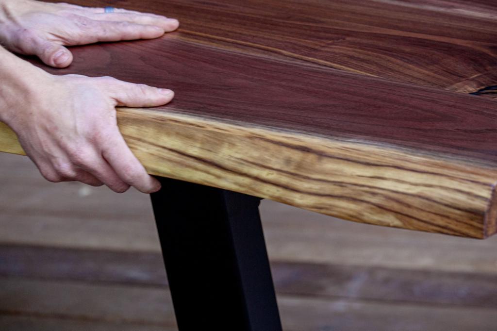 A close-up image of Hazel Oak Farms working on a live edge walnut industrial table.