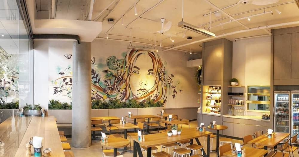 The Rough & Bare Mural by Hannah Adamaszek displays a girl immersed in nature and color.