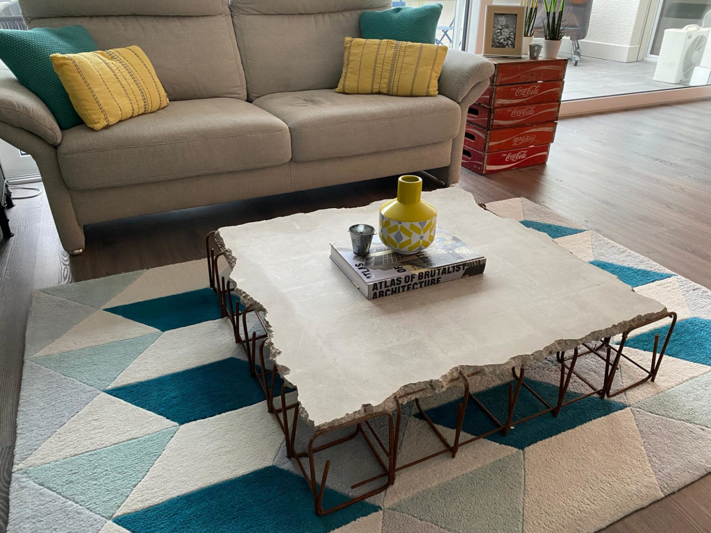 The Wade Table by Stephan Schmitz on Wescover has a concrete top and a geometric metal configuration holding it up.